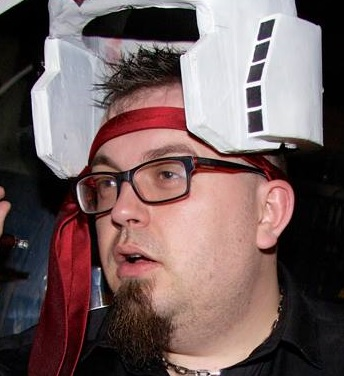 A photograph of Alan Teader, one half of Mid Game Crisis. He is wearing a Gundam Helmet and a tie as a headband