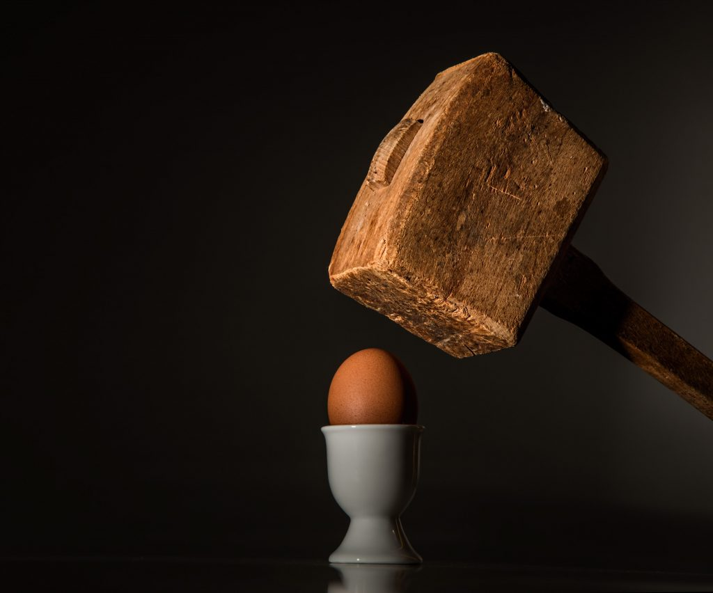 A large wooden mallet positioned above an egg, on black backgroun