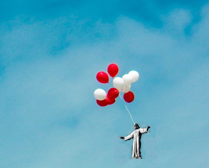 A photoshopped image of a statue of Jesus, being carried by balloons