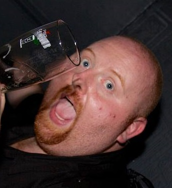 A photograph of Jamie McLellan, one half of Mid Game Crisis. He is smiling, very red in the face and is holding a glass which clearly contains beer.