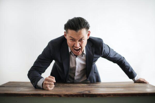 angry man slamming fist on desk